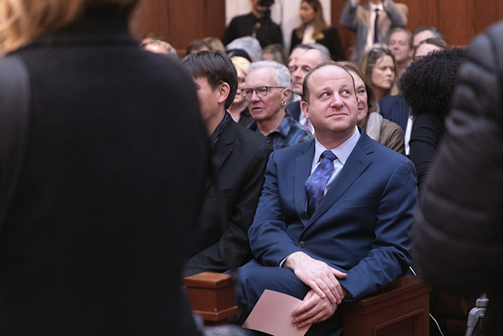 Governor Jared Polis smiling in a sea of people inside the Denver Capitol