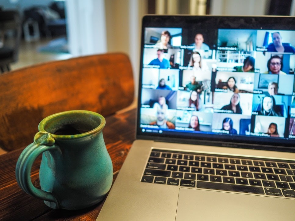 A coffee cup next to an open laptop with a video call on screen