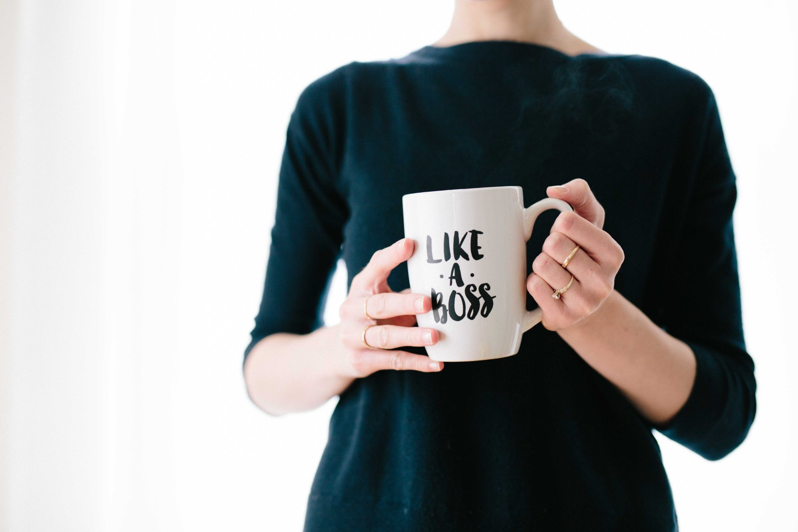 "woman holding a coffee cup that says ""like a boss"""